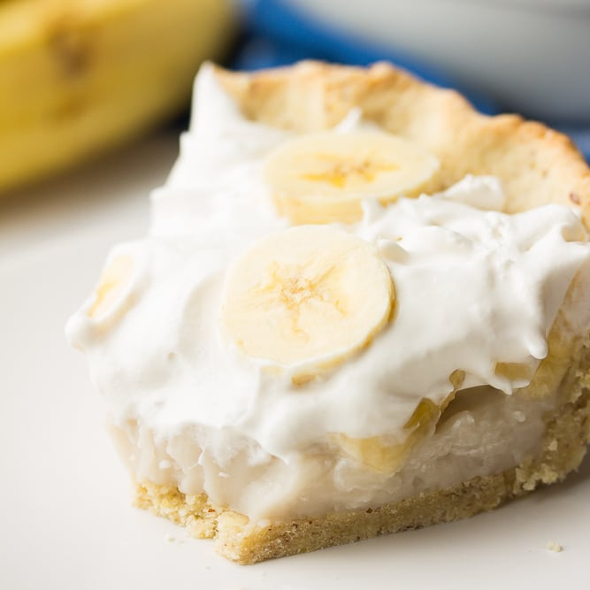 square image of creamy pie with bananas and bite taken out of it