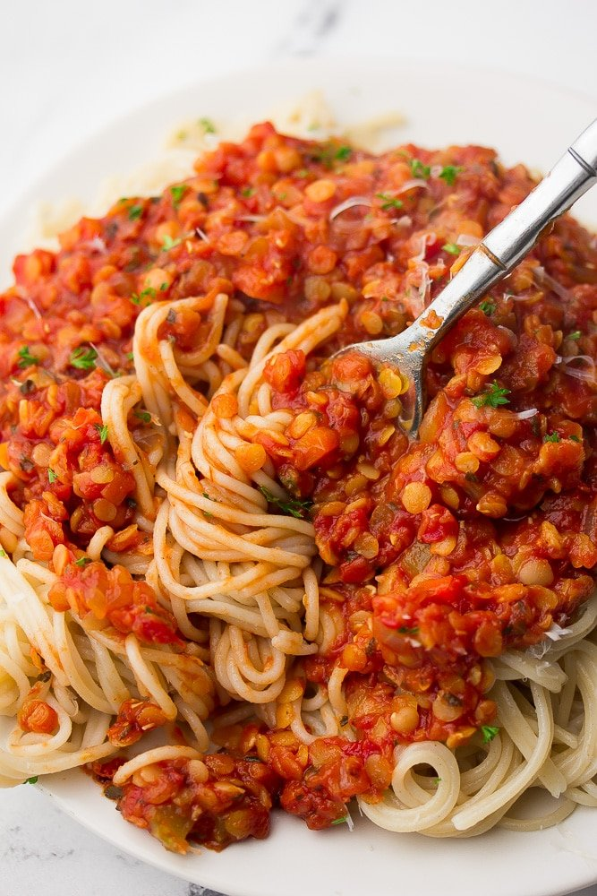 a fork swirling sauce and spaghetti around it on a plate