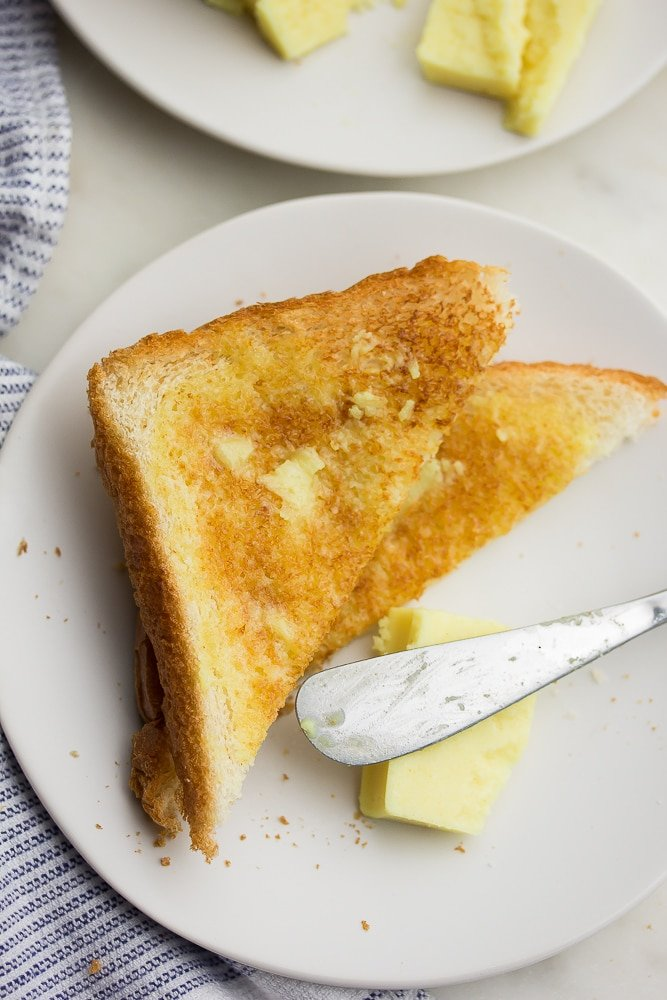 showing a piece of white bread toast with melted butter on it, knife nearby