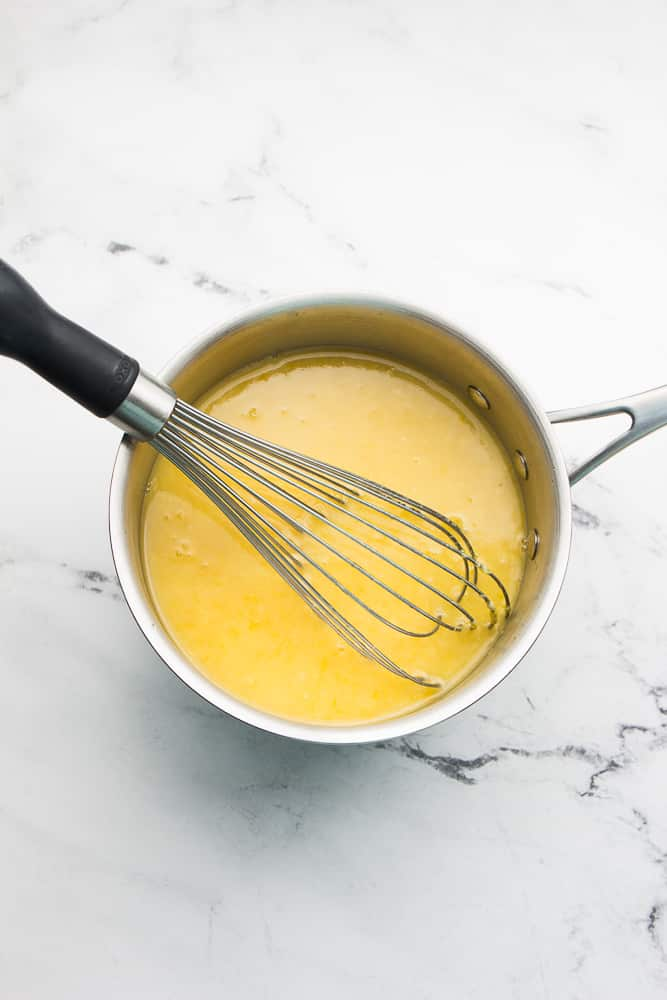 pan of yellow mixture with whisk in it