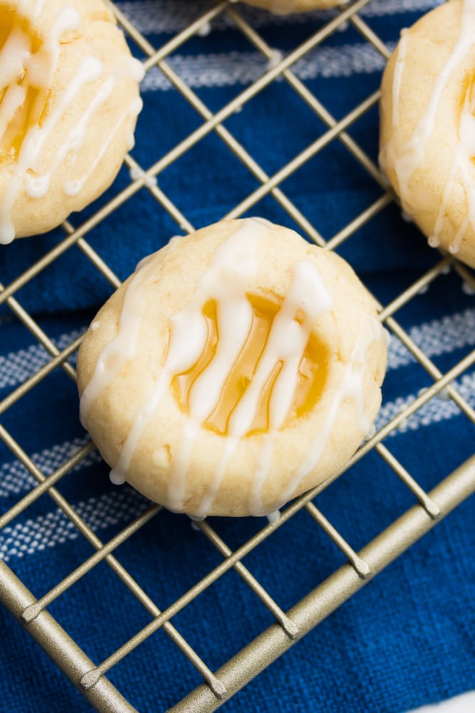 a close up of one vegan lemon shortbread cookie on a cooling rack with a blue towel underneath