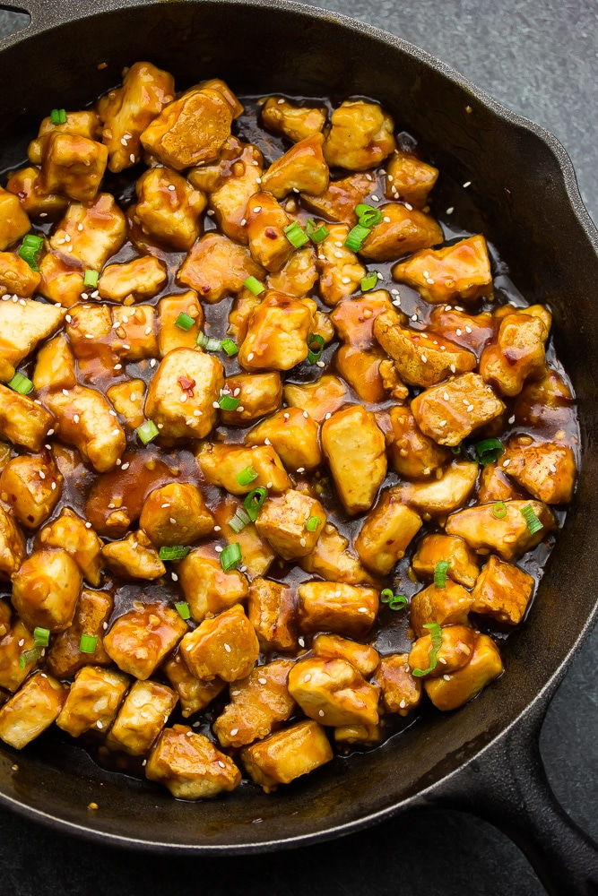 tofu simmering in skillet with the general tso's sauce