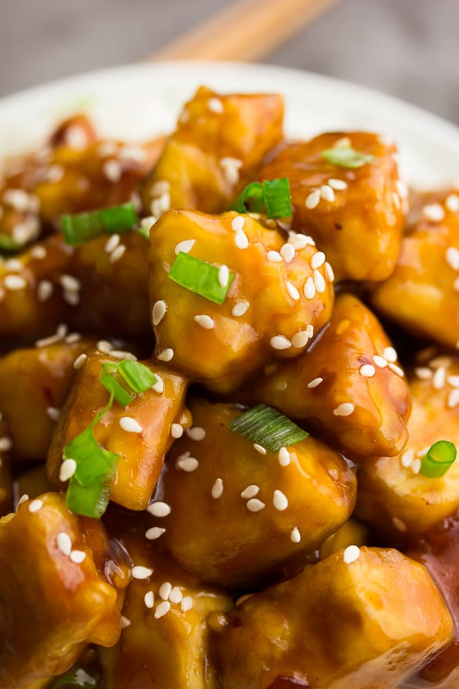 a close up of tofu with sesame seeds and chives