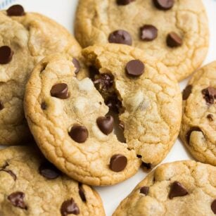 a square photo of a pile of chocolate chip cookies with the top one broken in half