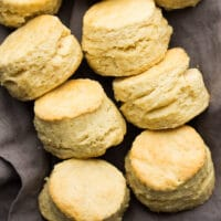 square photo of a group of buttermilk biscuits on a gray towel