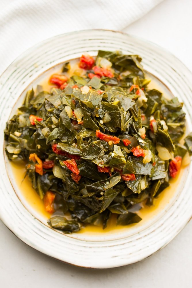 plate full of cooked collard greens with sun dried tomatoes