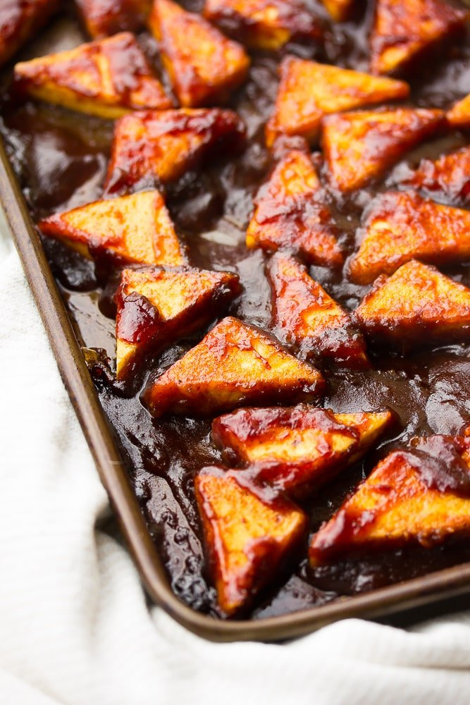 close up side shot of triangle tofu pieces with bbq sauce on them, cooked