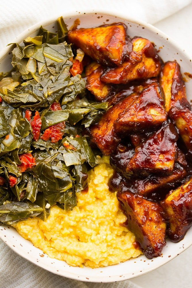 very close up of bbq tofu, collard greens and grits in a bowl