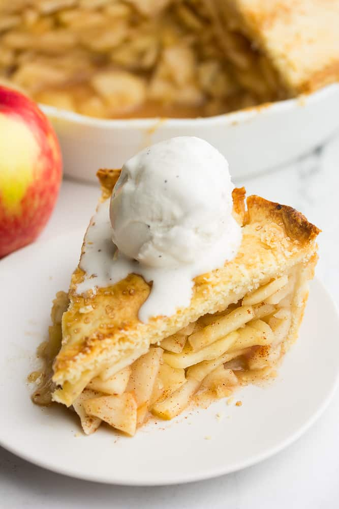 a piece of vegan apple pie on a plate with vanilla ice cream on top, melting