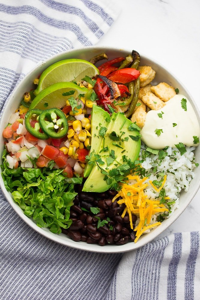 bowl with burrito bowl ingredients in it: rice, beans, queso, avocado, tofu.