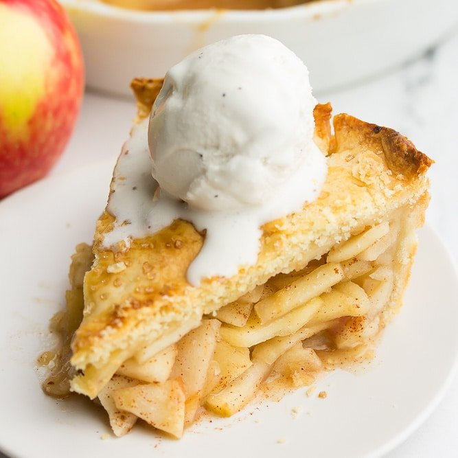 square image of apple pie with ice cream on top