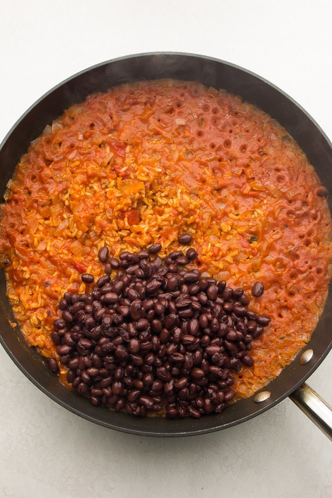 pan with red rice, adding black beans to it