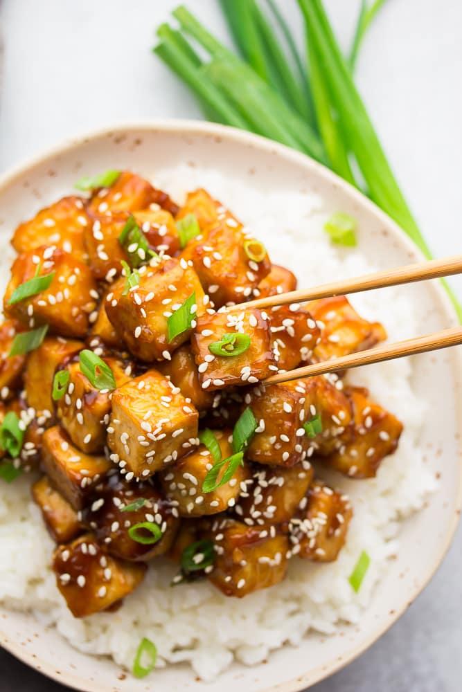 chopsticks grabbing tofu from bowl