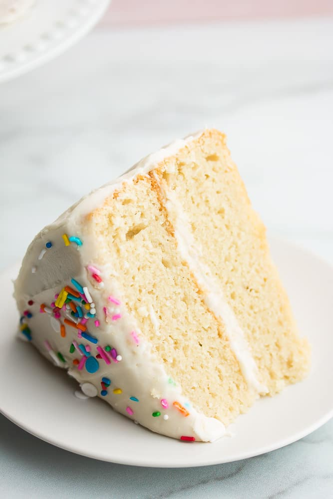 Close up of a slice of white cake with sprinkles on top on a white plate