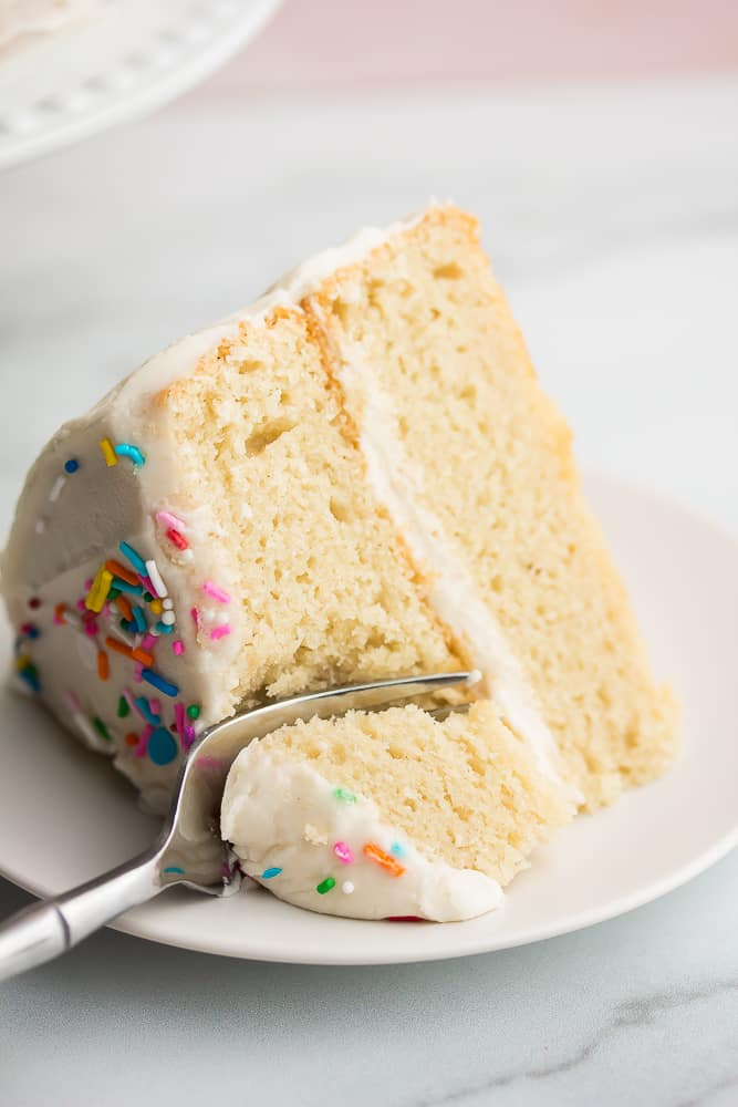 Close up of a slice of white cake with a fork taking a bite
