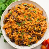 square image of a bowl of rice and beans, cilantro and tomatoes on the side