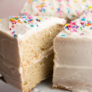 Close up of a slice of vanilla cake with sprinkles on top being removed