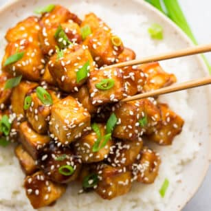 square image of a bowl of rice and saucy tofu, sesame seeds and green onions on top