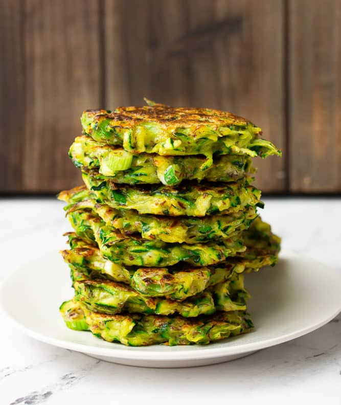 stack of vegan zucchini fritters on a white plate