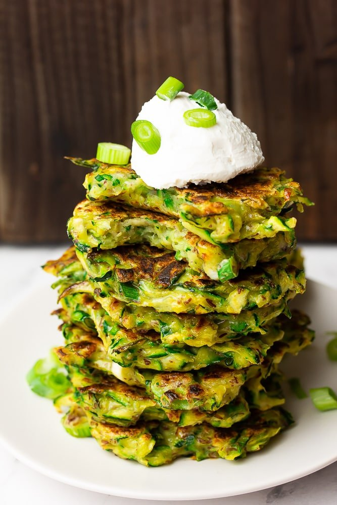 stack of fritters that are green with sour cream on top and chives