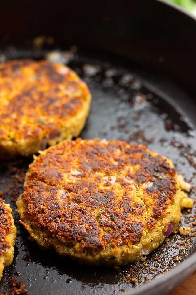 cast iron pan with burgers in it, that look vegetarian bean based