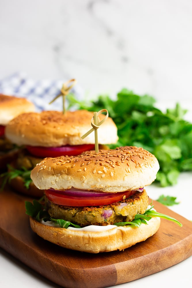 three burgers in a row on a cutting board, white marble background