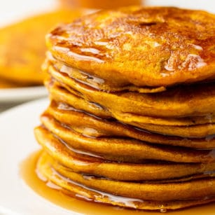 square image of stack of pumpkin pancakes on white plate