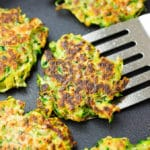 square image of a pan with fritters, one being lifted out with a spatula