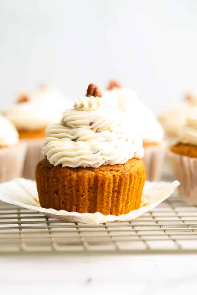 an orange cupcake with frosting, more in background, pecan on top