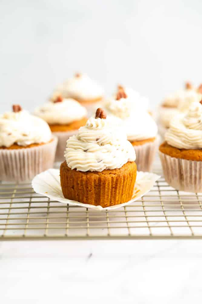 lots of pumpkin cupcakes with pecan pieces on top