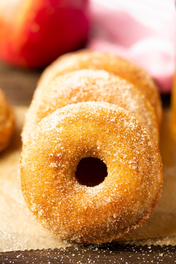 horizontal stack of sugar glazed donuts, apples in background