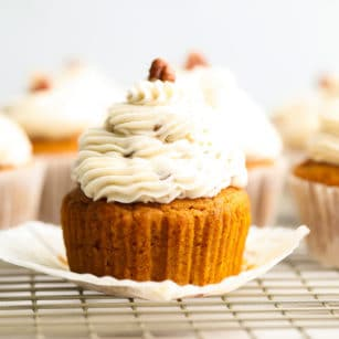 square image of close up cupcake from the side with pecans on top