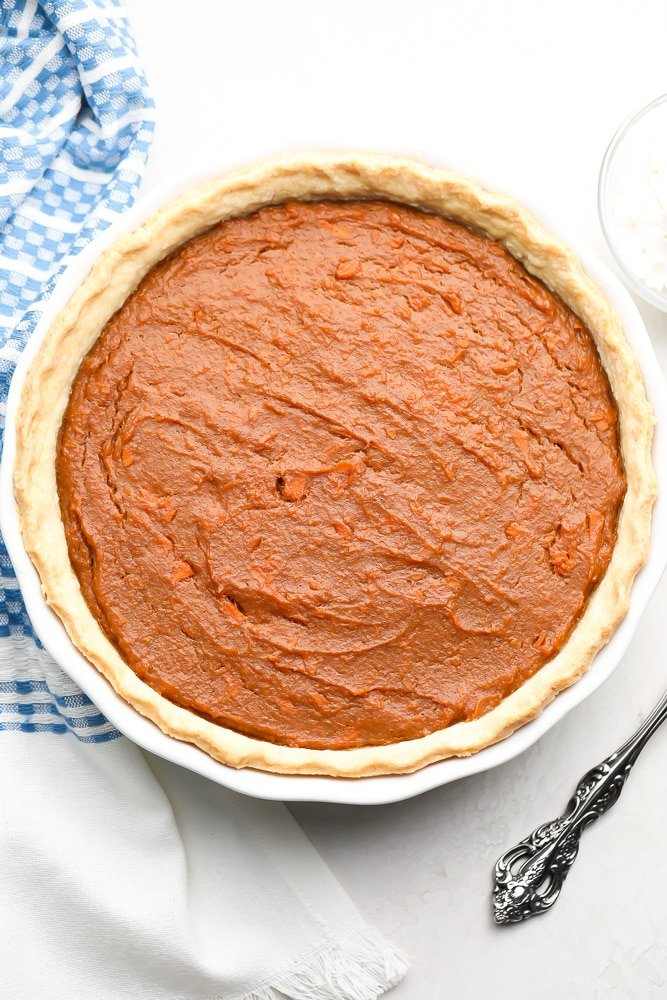 whole vegan sweet potato pie with blue towel in background