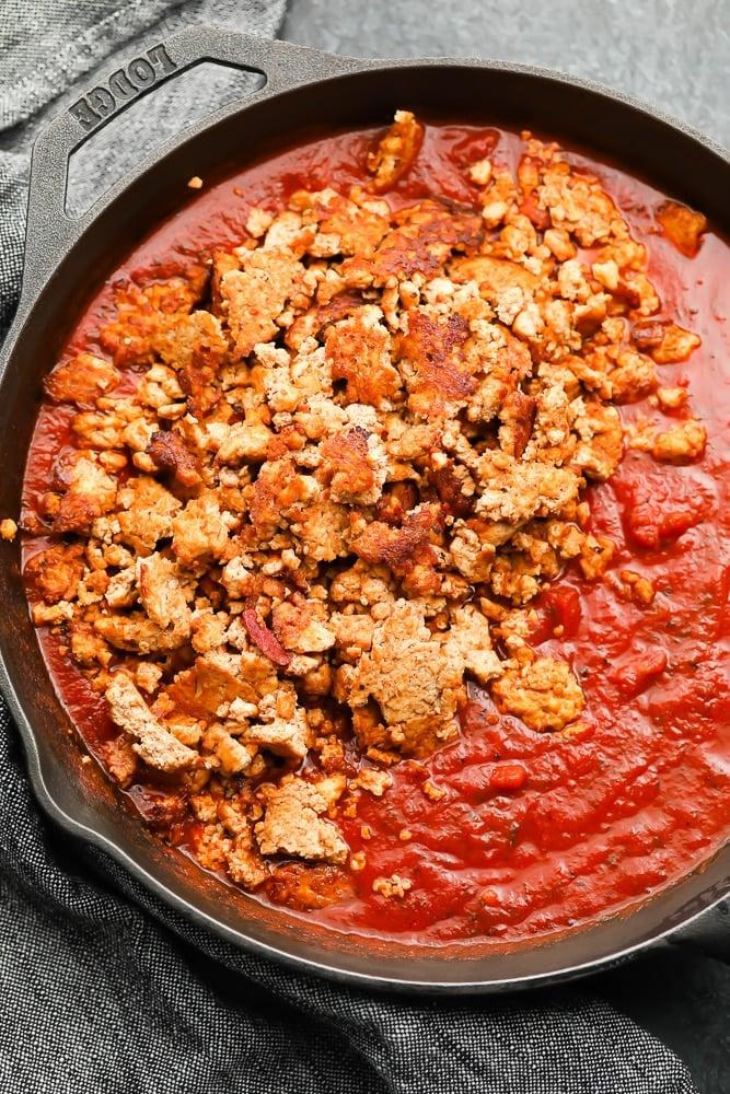 cast iron pan with marinara sauce and tofu crumbles