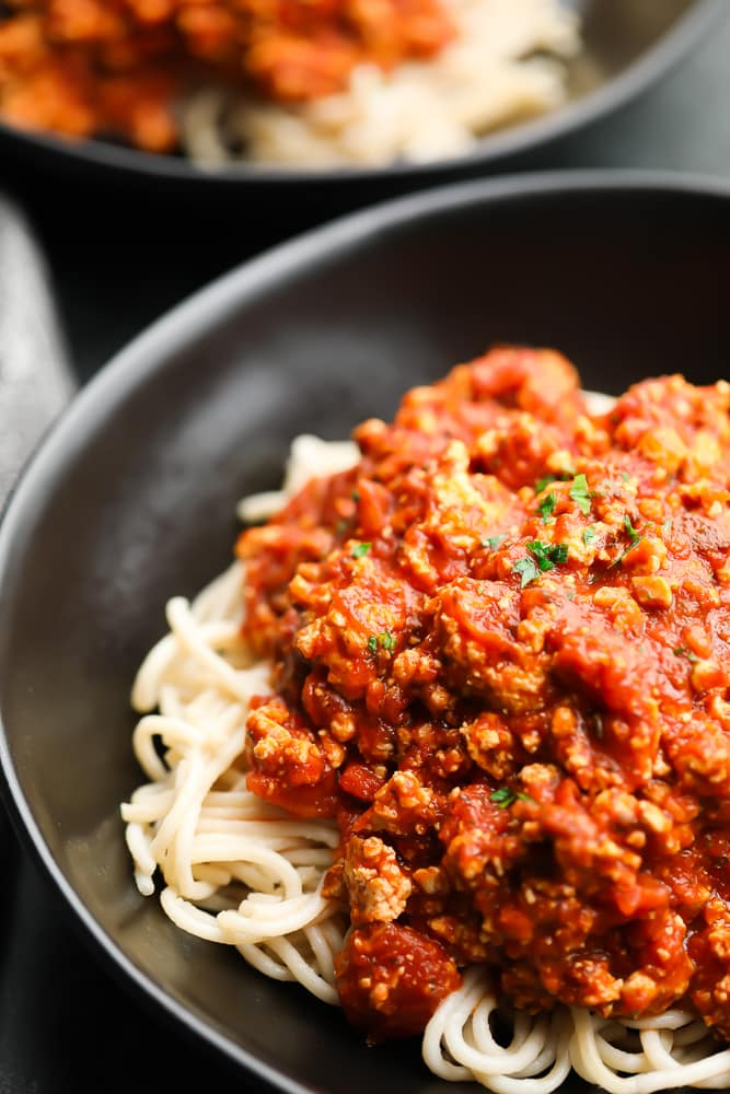 close up of vegan bolognese sauce in black bowl over pasta