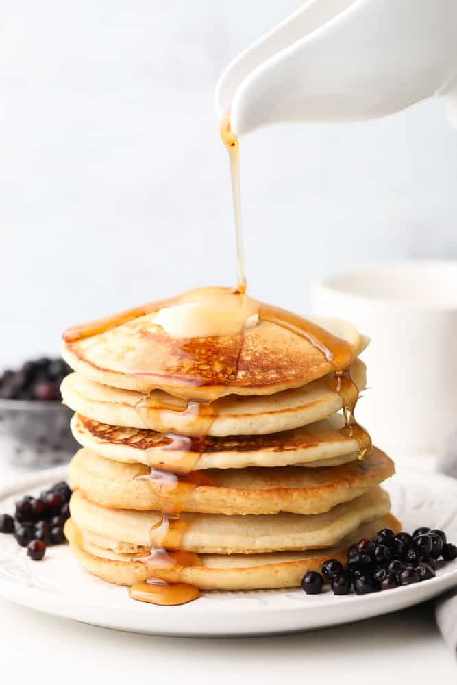syrup being poured onto a stack of golden pancakes