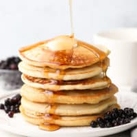 square image of pancake stack with syrup being poured, blueberries around them
