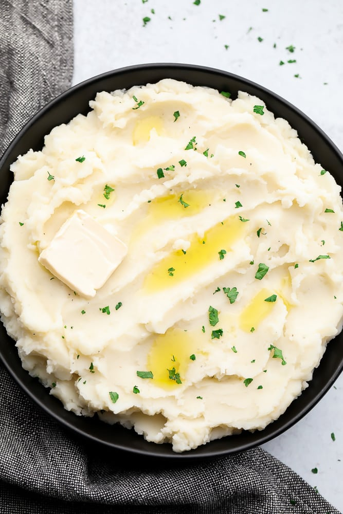 black bowl full of mashed potatoes with butter