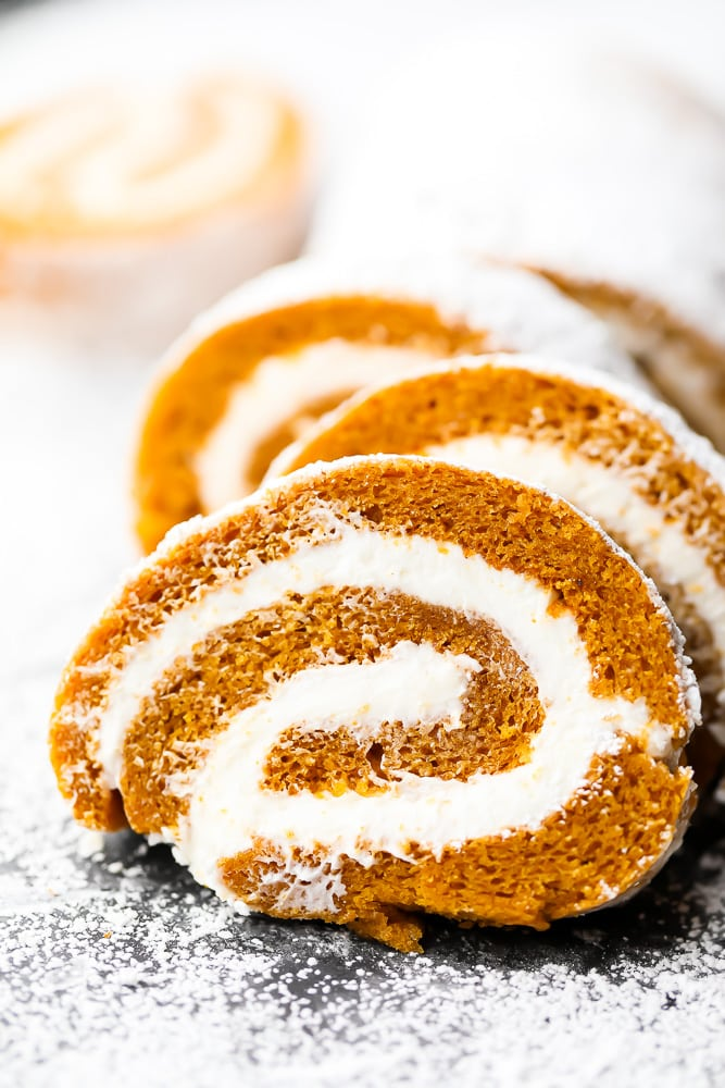 slices of pumpkin roll cake with powdered sugar all around