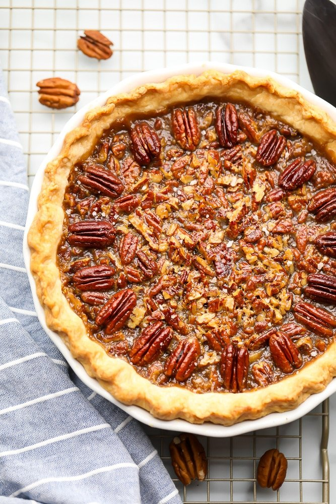 whole cooked pecan pie with blue towel on a cooling rack