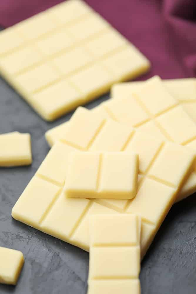 many broken pieces of white chocolate, laying on top of each other