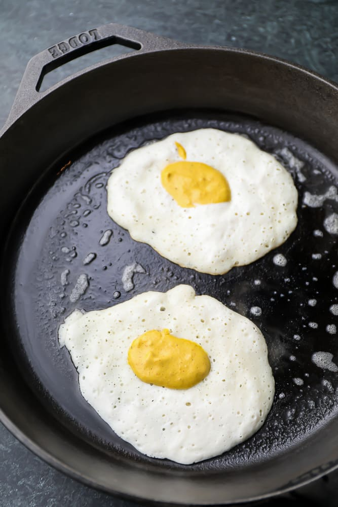 uncooked white fried eggs in a pan with a yolk