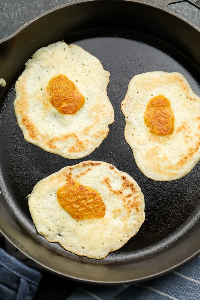 looking down on three eggs in a cast iron pan