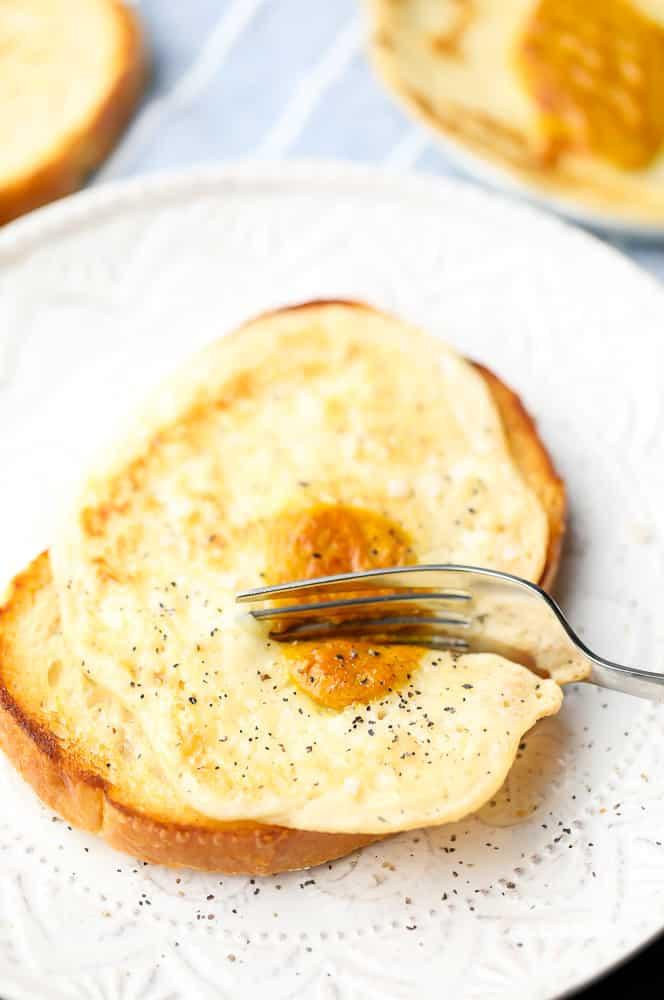 a fork cutting a vegan egg on toast