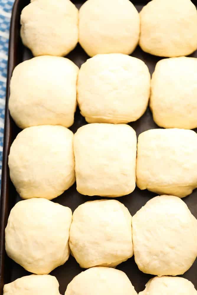 pan full of dinner roll dough in balls