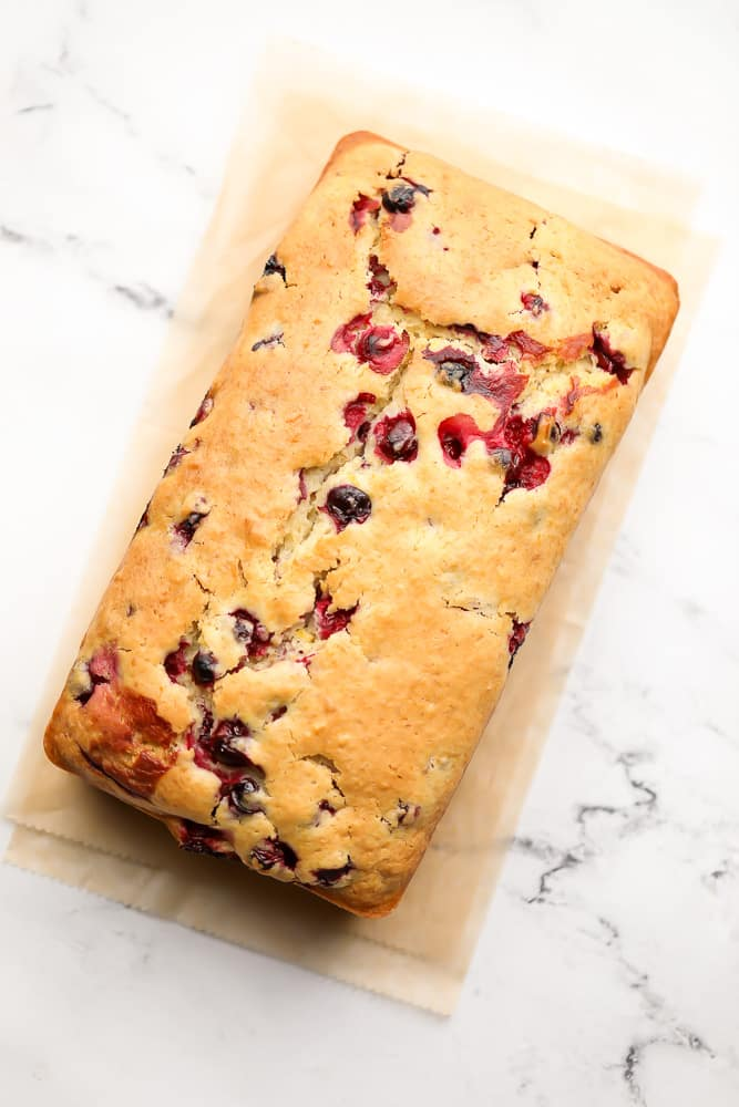 cooked orange loaf with cranberries, on marble backdrop