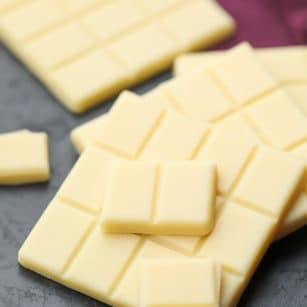 square image of white chocolate, burgundy towel in background