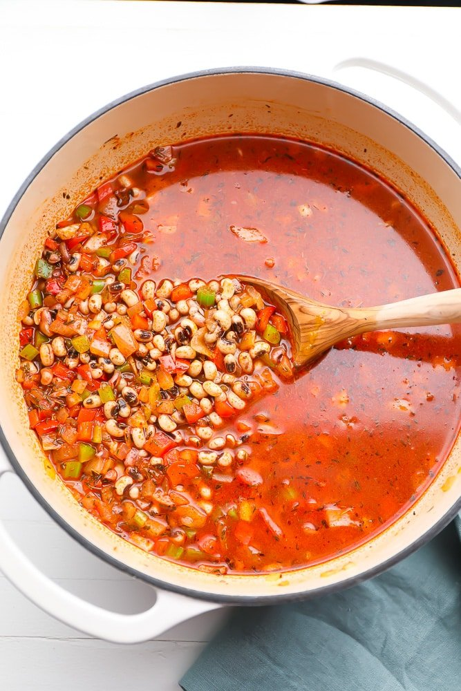 beans not yet cooked in a pot with red broth