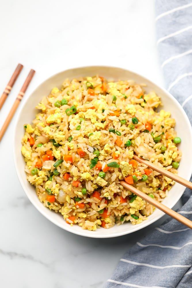 bowl of fried rice with chopsticks, white background