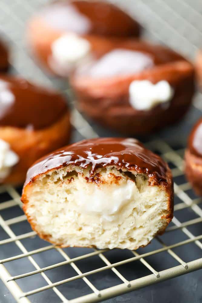 cut open boston cream donut on rack, more in back
